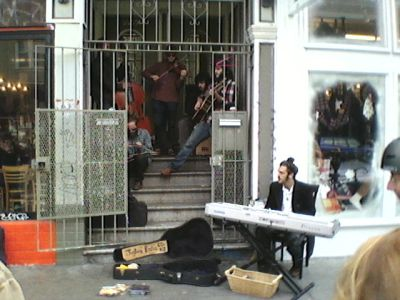 Five musicians in an entranceway, one keyboardist on the sidewalk, with an open guitar case.